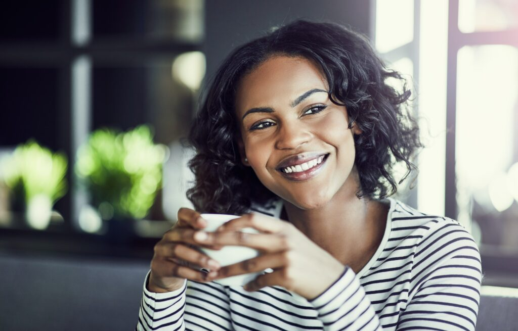 Smiling young African woman enjoying coffee in a cafe