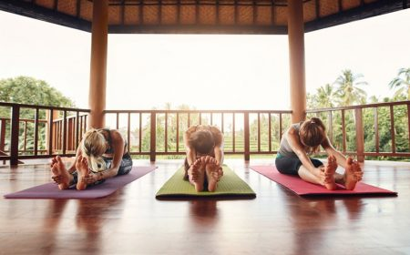 three-women-practicing-paschimottanasana-pose-at-y-P7F46KA.jpg