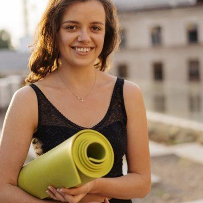 woman-holds-yoga-mat-Z8SHYBG.jpg
